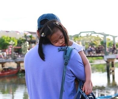 Cô bé người Nhật ngủ ngon giấc trên lưng cha trong khi đi dạo ở phố cổ Hội An.
